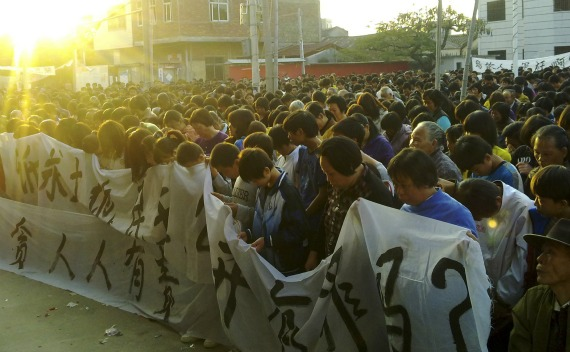 Residents observe a moment of silence for a local leader who died in police custody, during a demonstration in Wukan village on December 13, 2011.