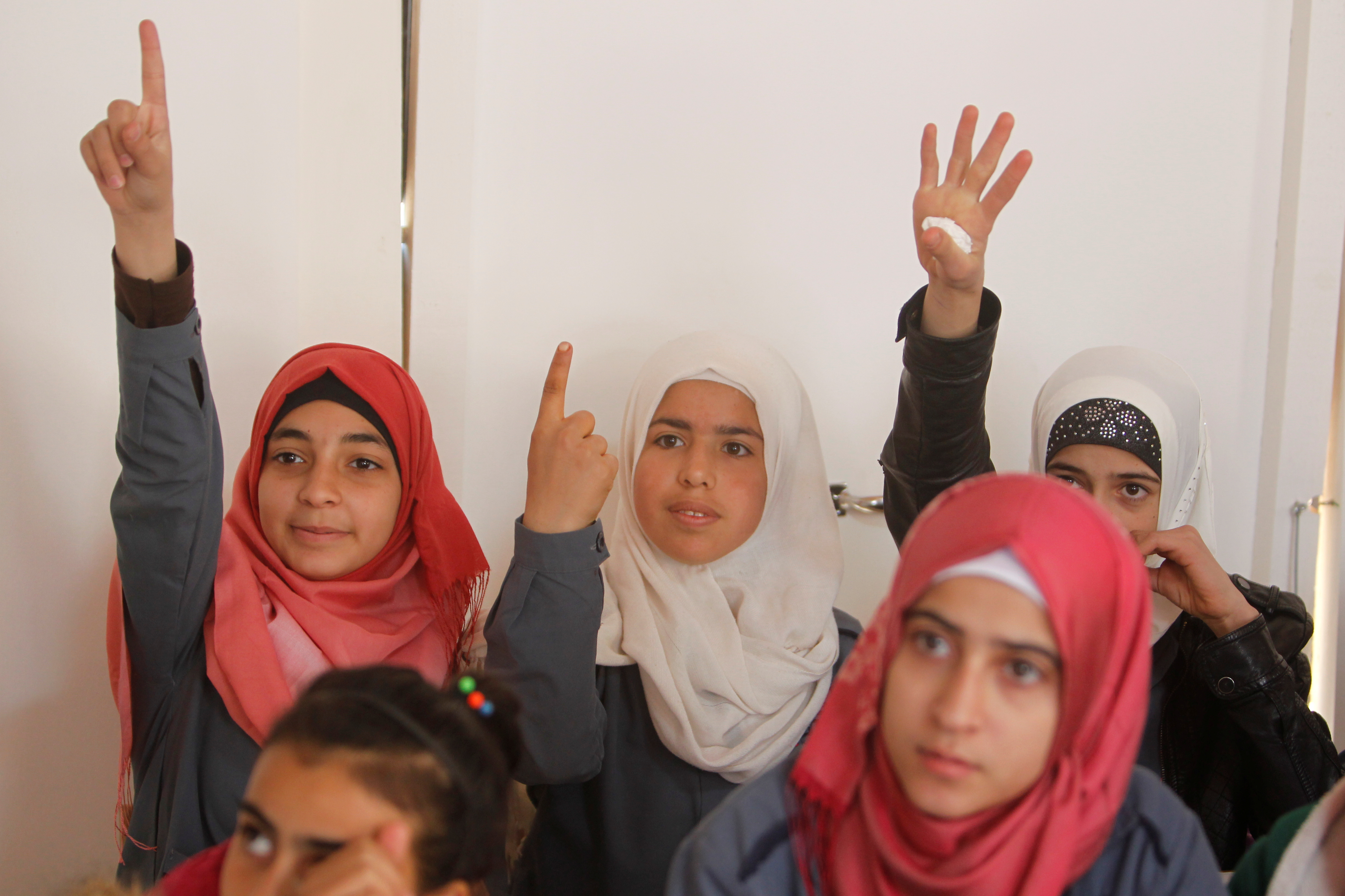 Syrian refugee girls gesture as they sit inside a classroom at a school for Syrian refugee girls in Lebanon, October 19, 2017.
