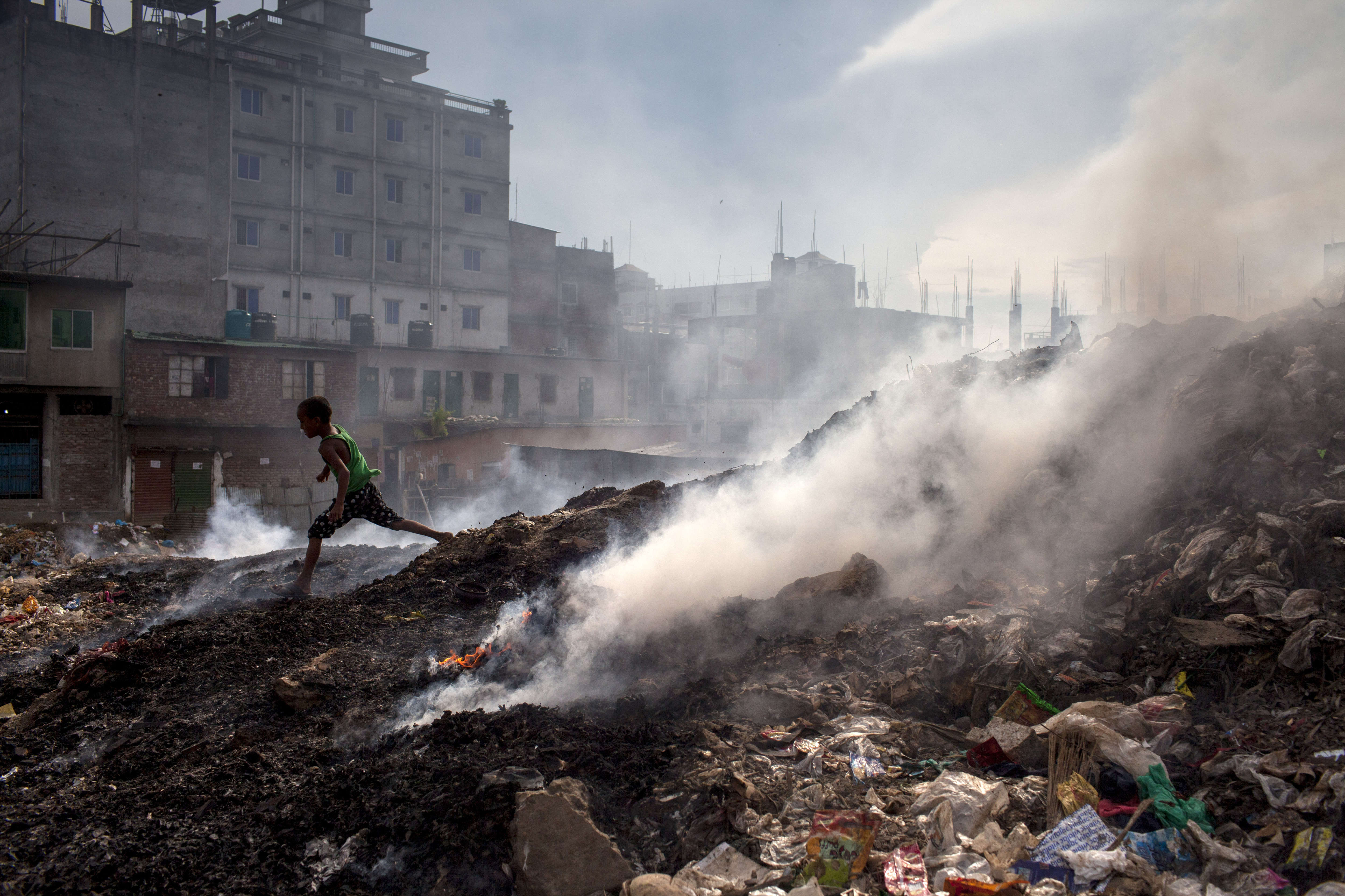 A child runs beside the waste-burning area of a dump in Dhaka, Bangladesh.