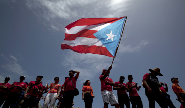A man waves a Puerto Rican flag during a protest in a May 2015 protest in San Juan. University students and employees took to the streets to oppose proposed cuts to public university budgets.