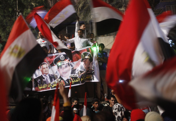 Protesters cheer with Egyptian flags and a banner of army chief Abdel-Fattah El-Sisi.