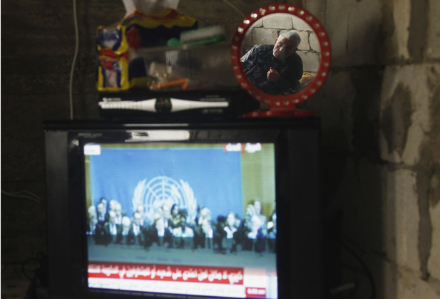 Syrian refugee reflected in a mirror as he watches the Geneva II peace conference on television at the port city of Sidon, southern Lebanon.