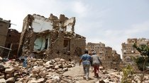 People walk past a house destroyed by an airstrike in Sanaa, Yemen.