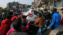 Demonstrators overturn a car during a protest in Jammu