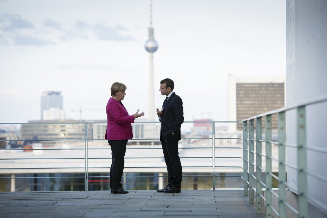 German Chancellor Angela Merkel talks with newly-elected French President Emmanuel Macron on the terrace, with a view of the television tower in the background