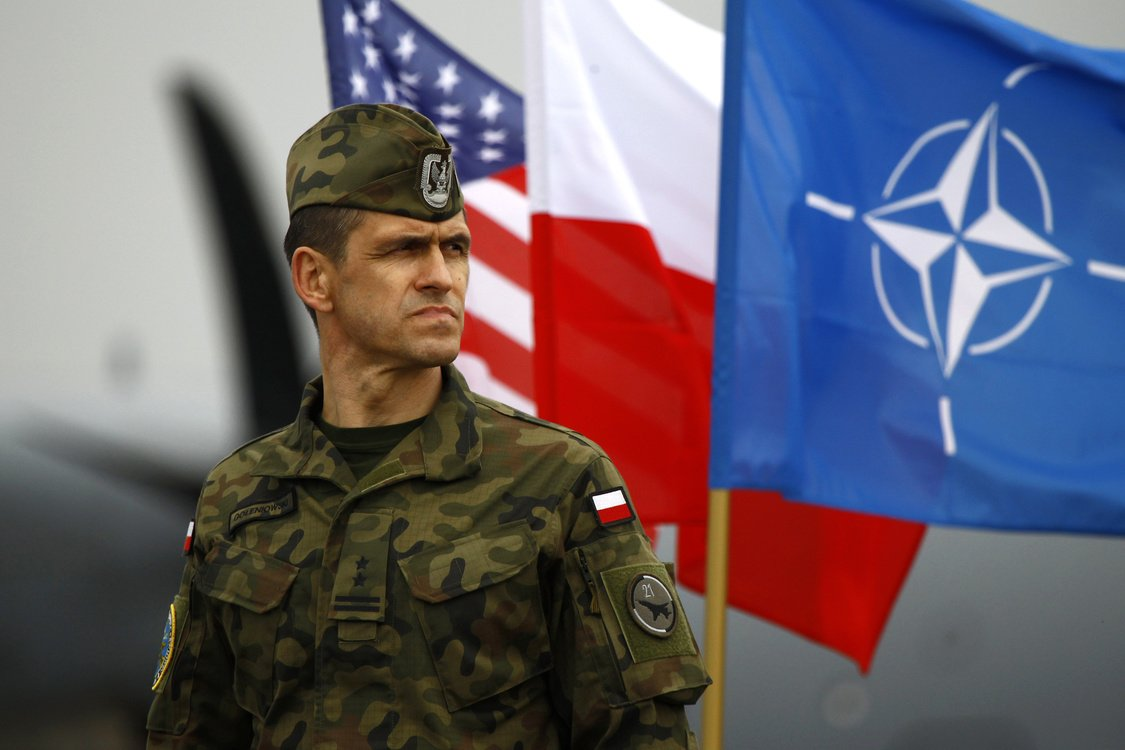 A Polish soldier stands near U.S. and Poland's national flags and a NATO flag