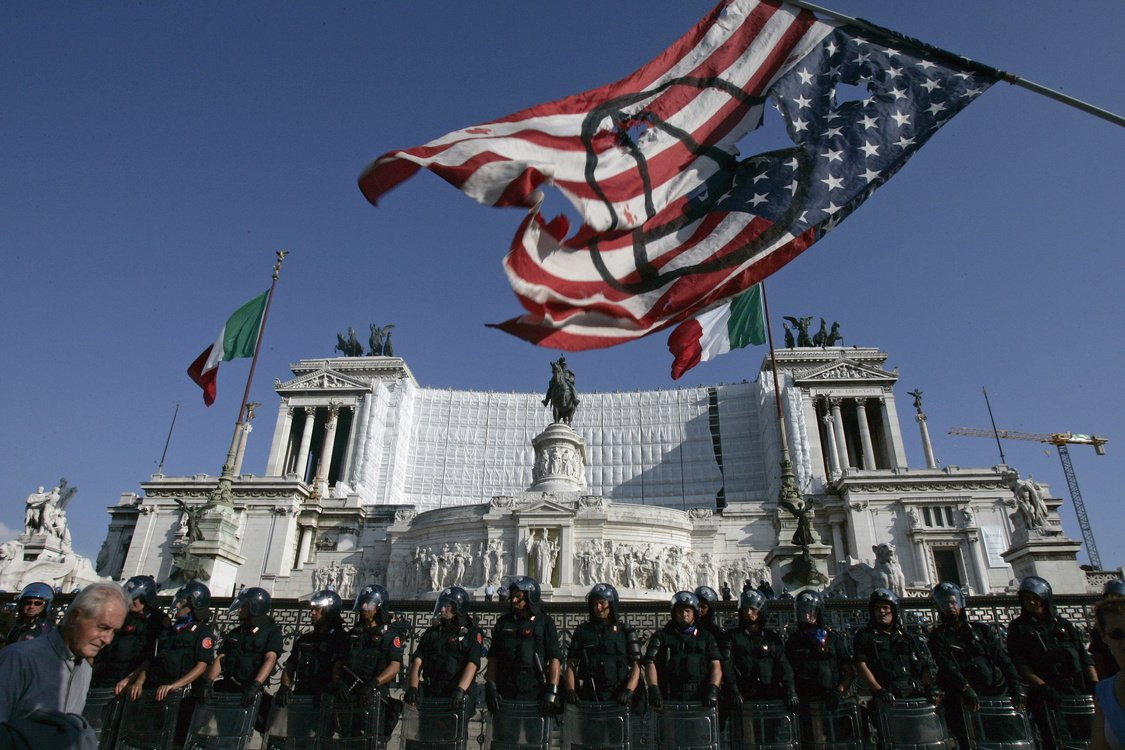 A protester waves a flag as Italian Police stand guard during a demonstration against the visit by U.S. President George Bush in Rome