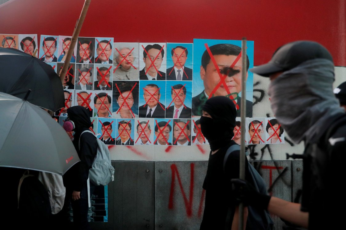 Anti-government protesters walk past defaced pictures of Chinese President Xi Jinping and other members of the government, in Hong Kong