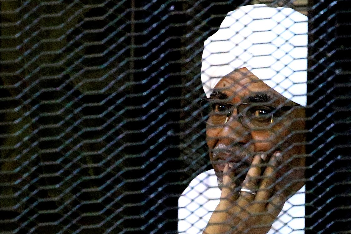 Sudan's former president Omar Hassan al-Bashir sits inside a cage at the courthouse where he is facing corruption charges