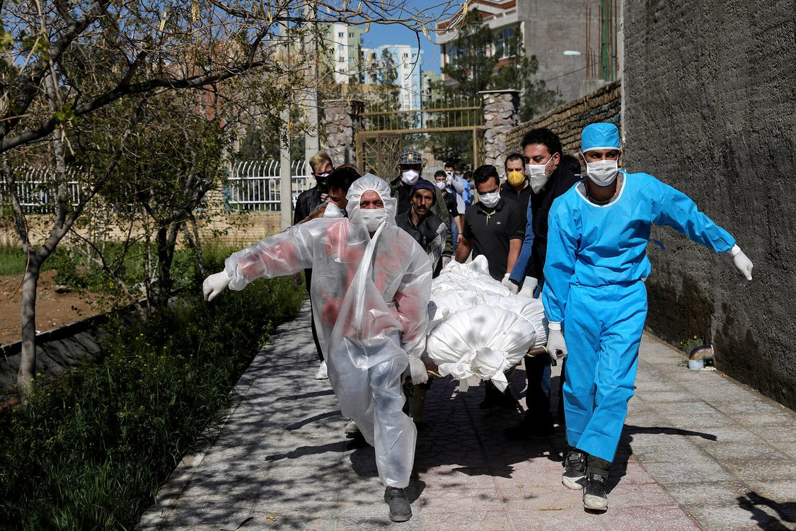 people carry the body of a victim who died after being infected with the new coronavirus at a cemetery just outside Tehran, Iran.