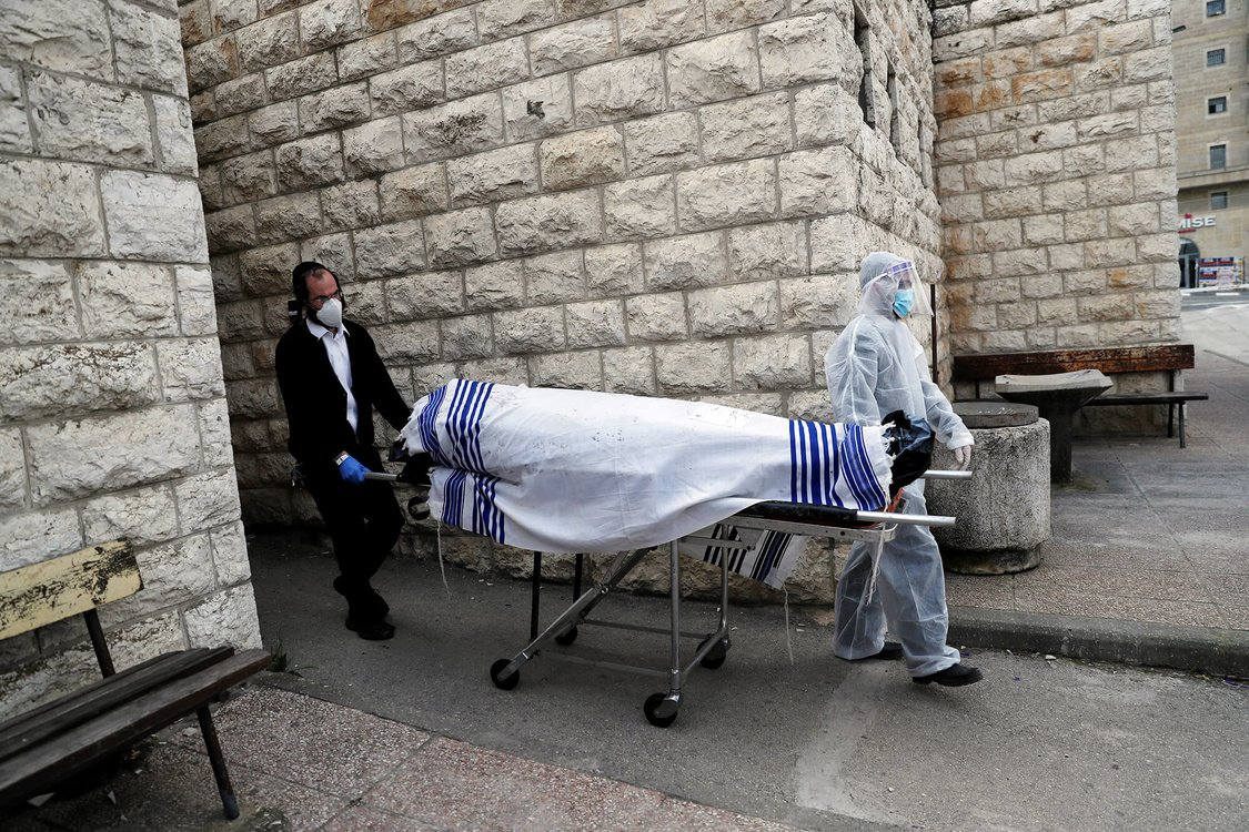 Workers of Jewish Burial Society wear protective gear as they carry the body of a victim of coronavirus disease