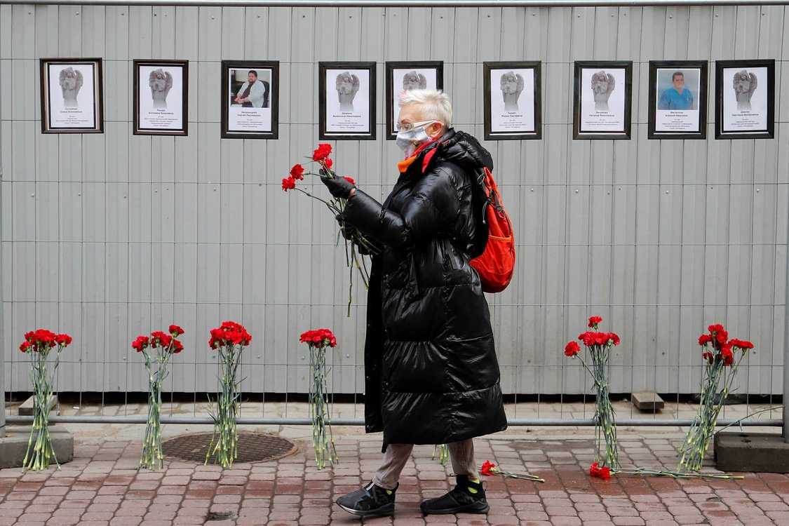 A woman wearing a protective mask holds flowers near a makeshift memorial for medics, who reportedly died in Saint Petersburg and Leningrad Region in the times of the coronavirus disease