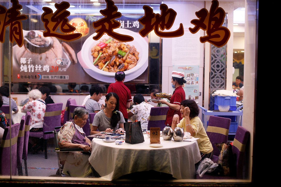 A family seen through a restaurant window, sits for dinner in Guanghzou, China.