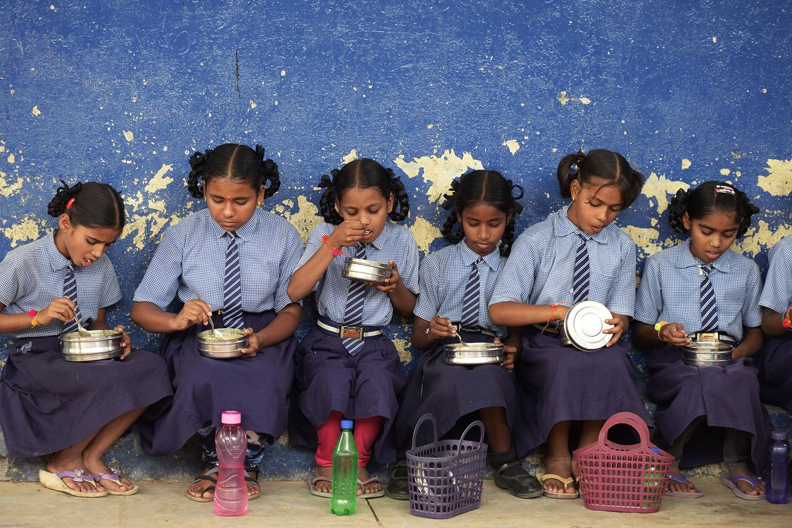 Girls sitting next to each other eat their mid-day meal at a high school in Hyderabad, India