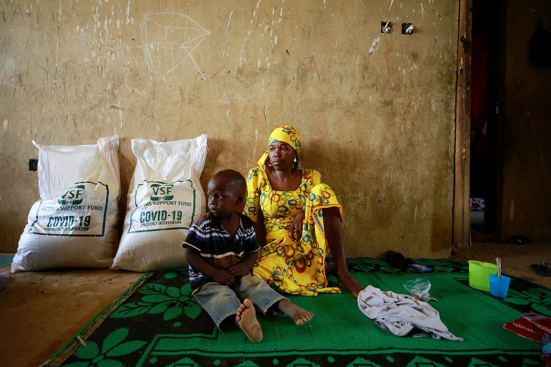 Woman and child sitting on floor on green carpet receive bags of food.