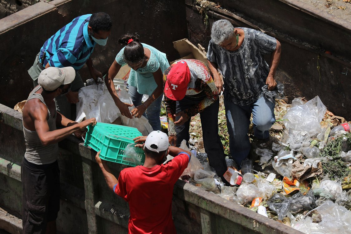 People search for food at a garbage container during the closing hour at the Coche wholesale market in Caracas, Venezuela.