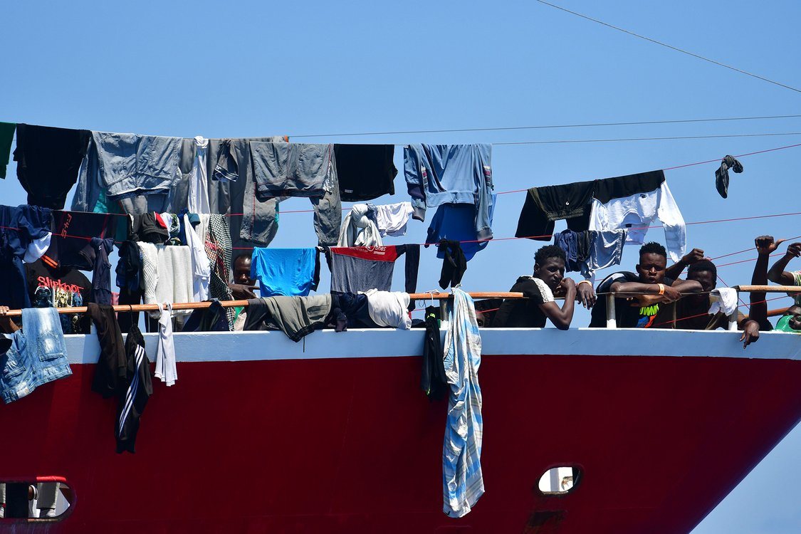 Migrants look out from a tourist ship at Hurd's Bank on June 2, 2020.