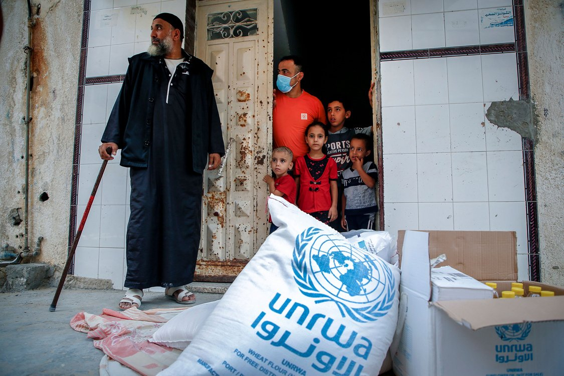 Members of a Palestinian family, some clad in mask due to the COVID-19 coronavirus pandemic, stand through the door of their home as they receive food aid provided by the United Nations Relief and Works Agency for Palestine Refugees (UNRWA) in Gaza City