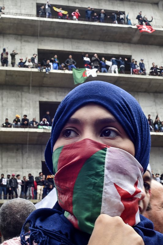 A woman covers her face with the national flag, as Algerian protesters demonstrate in the capital Algiers