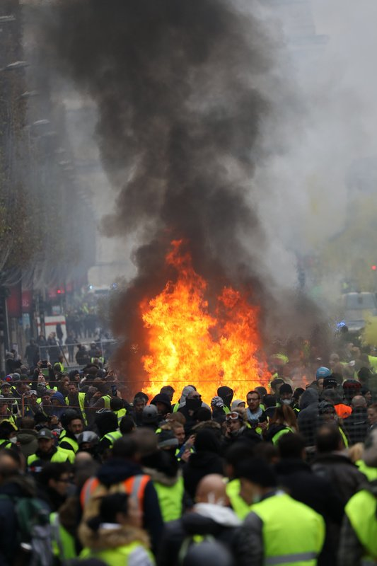 Protesters wearing yellow vests protest against rising fuel prices on the Champs-Elysees avenue