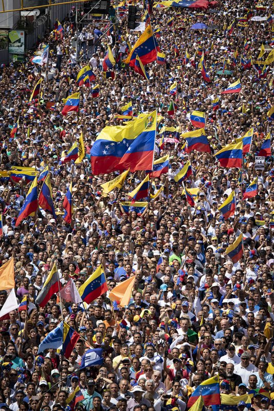 Demonstrators waving Venezuelan flags.